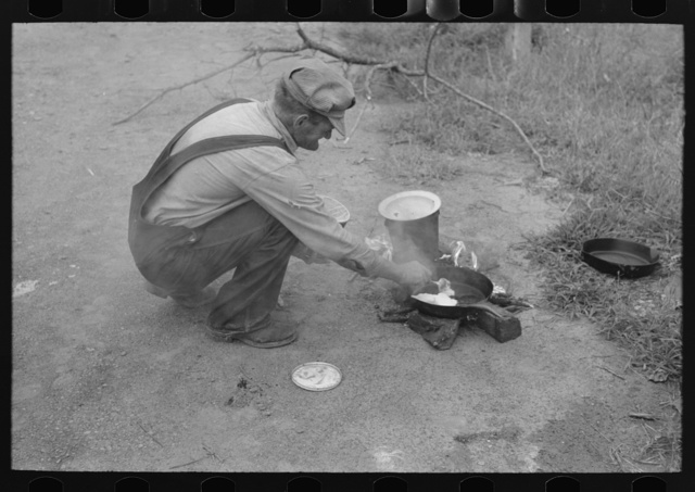 Elmer Thomas putting lard into the frying pan. At roadside camps each person in a migrant camp has his own duties. In this case, Mr. Thomas is attending the fire. There are a certain number of assignments which have been given him, of which this is one. Near Henrietta [i.e., Henryetta,] Oklahoma