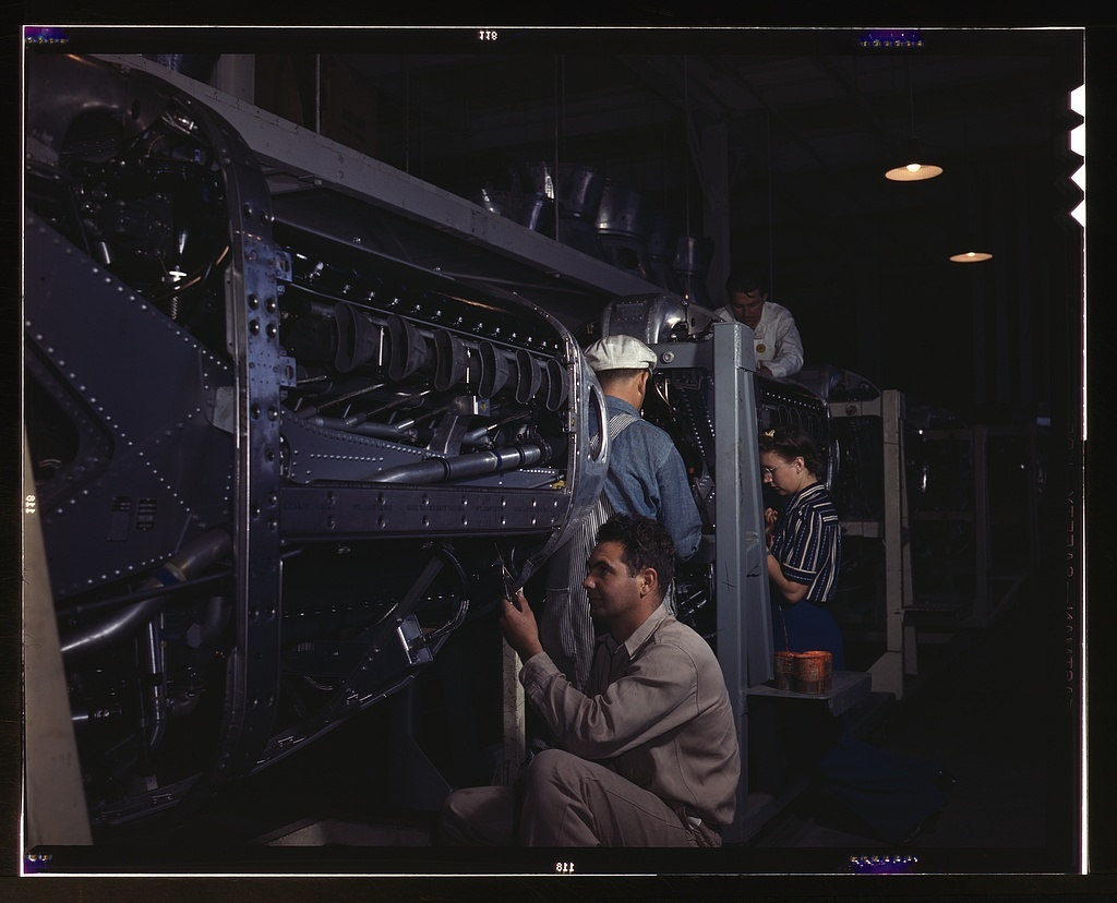 Employees at North American Aviation, Incorporated, assembling the cowling on Allison motors for the P-51 fighter planes, Inglewood, Calif.