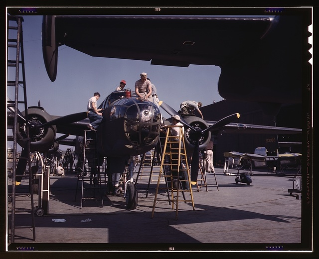 "Employees on the ""Sunshine"" assembly line at North American's plant put the finishing touches on another B-25 bomber, Inglewood, Calif. In addition to the battle-tested B-25 (""Billy Mitchell"") bomber, used in General Doolittle's raid on Tokyo, this plant produces the P-51 (""Mustang"") fighter plane which was first brought into prominence by the British raid on Dieppe"