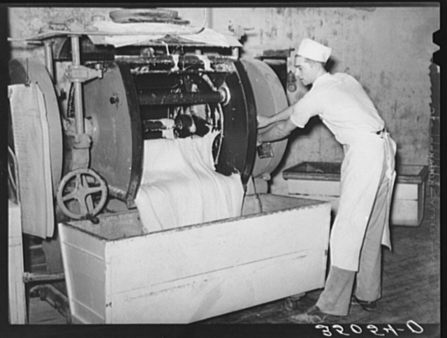 Emptying the dough from mixing machine into the moveable rising vats. Bakery, San Angelo, Texas