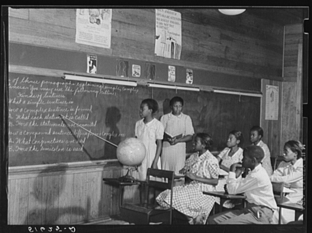 English lesson in sixth and seventh grade school room. Selma Sutton at board with teacher, Miss Jessie West Greene. Flint River Farms, Georgia