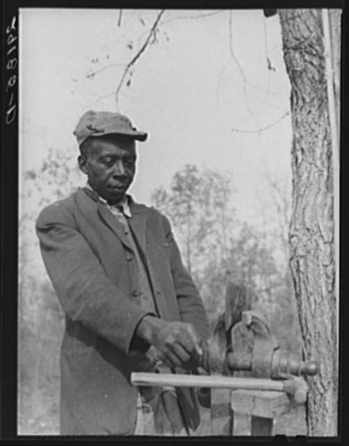 Evicted sharecropper fixes his axe. Butler County, Missouri
