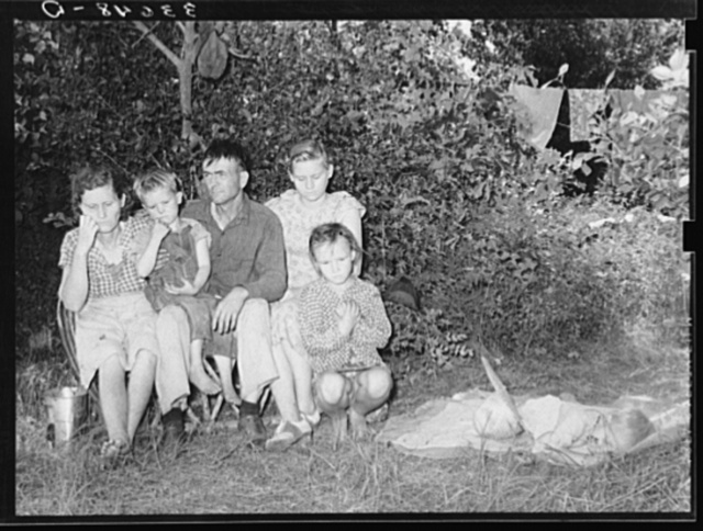"""Family of migrant agricultural day laborers camped near Spiro, Oklahoma. The man and his wife had farmed in this vicinity for many years. However, they had always been renters. They have found it increasingly difficult to find land and house for rent. They had moved to the river bottom where they were camping out while working in the nearby fields. The mosquitoes were bad. They had to move to higher ground by the roadside.  The entire family--mother, father and six children--had malaria. When the man was asked if there was much malaria among the people, he replied, """"Yes, they have always started chillin' and they'll keep achillin' till frost, them that don't die."""" The father and two children were chopping cotton for a dollar a day. The father said """"that as soon as they got a few dollars ahead it came a rain and they spent their money before it was dry enough to work again."""" They had a car and were going on to California as soon as they had enough money. The woman's sister is living in Bakersfield, California, and they want to get out there. """"They ain't doing much, but he's making a living and I ain't making it here."""""""