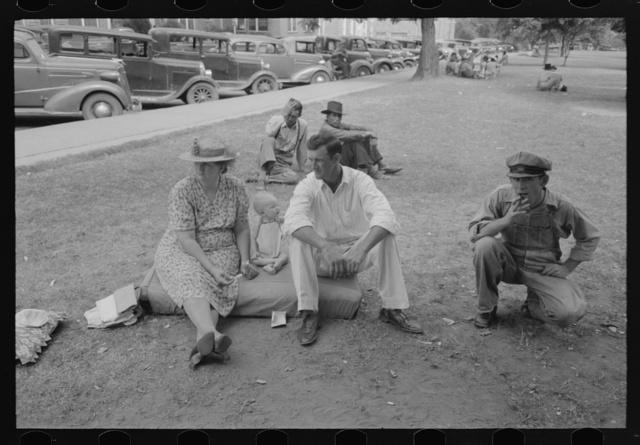 Farm people sitting on automobile cushion in square, Tahlequah, Oklahoma