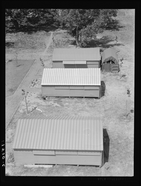 Farm Security Administration (FSA) camp for migratory agricultural workers. Farmersville, California. Shows prefabricated steel shelters which have been erected to replace tents as standard camp equipment in two of the California camps