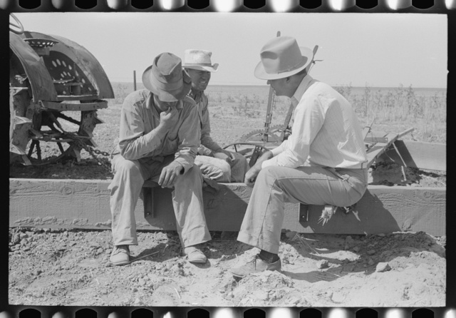 Farm Security Administration supervisor talking with two of the Davidson brothers who own a cooperative well made possible by FSA loan. Gray County, Kansas