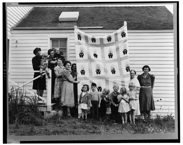 "Farm women of the ""Helping Hand"" club display a pieced quilt which they are making for the benefit of one of their numbers. Near West Carlton, Yamhill County, Oregon. General caption number 58-11"