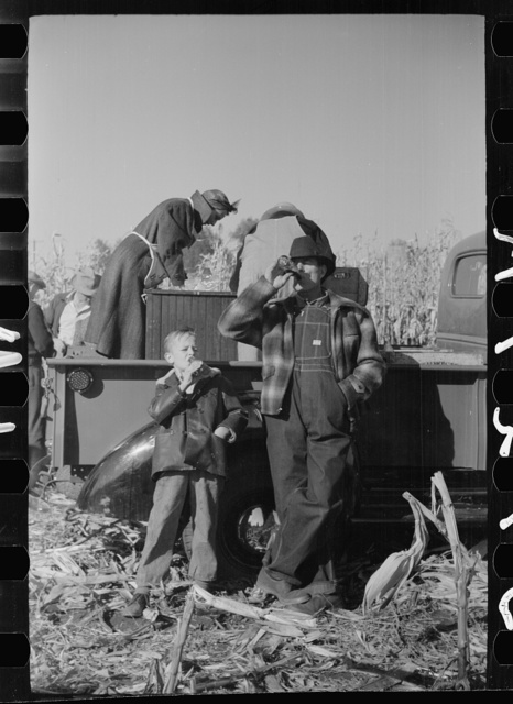 Farmer and son at refreshment stand, mechanical corn picker contest, Hardin County, Iowa