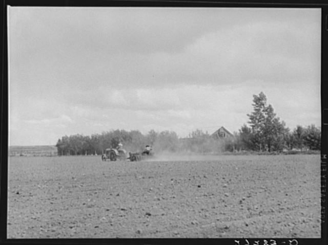 Farmer and wife operationg tractor and seed drill. Fairfield Bench Farms, Montana