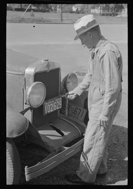 Farmer changing license plates, San Augustine, Texas