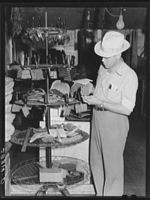 Farmer examines brushes for horses, cattle and hogs. Harness shop, Grundy Center, Iowa