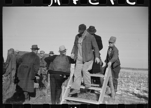 Farmers coming over a stile, at mechanical cornhusking contest, Hardin County, Iowa