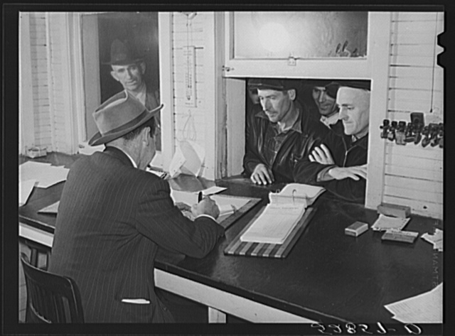 Farmers getting their checks in warehouse office after their tobacco has been sold at auction. Durham, North Carolina