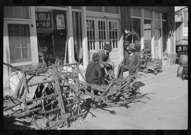 Farmers waiting around in front of farmer's supply company next to tobacco warehouse during auction sales, Durham, North Carolina