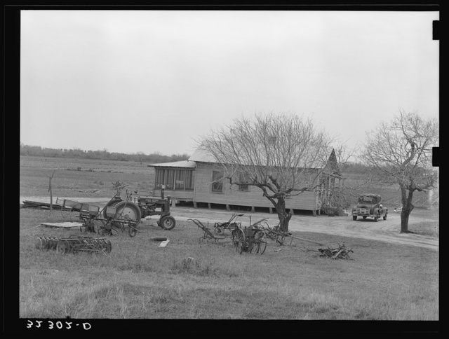 Farmhouse of small farmer near Santa Rosa, Texas. Tractor and rusting farm implements are in the yard, showing the changes in farming methods and also demonstrating that even the small farmers are using the new tractors and other mechanized equipment