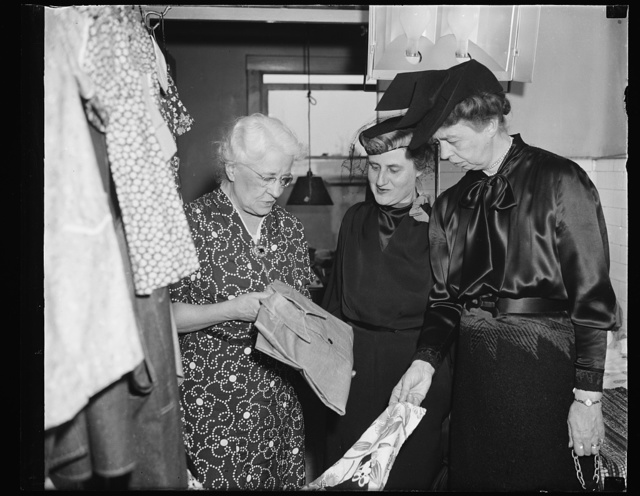 FIRST LADY AND MRS. MORGANTHAU SEE UNEMPLOYED TRADE TIME FOR CLOTHES AND FOOD, WASHINGTON, D.C. FEBRUARY 9. MRS. FRANKLIN D. ROOSEVELT AND MRS. HENRY MORGANTHAU TODAY VISITED THE SELF-HELP EXCHANGE HERE TO SEE EMPLOYABLE UNEMPLOYED HELPING EACH OTHER. MEMBERS PRODUCE GOODS WHICH ARE EXCHANGED TO OTHER MEMBERS THROUGH THE MEDIUM OF SCRIP. L TO R: MRS. J.A. HOVERT, LOANED BY CIVIC THEATER FOR PUBLICITY; MRS. ROOSEVELT; AND MRS. MORGANTHAU. THEY ARE EXAMINING GARMENTS MADE BY THE GROUP
