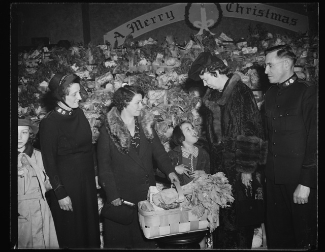 FIRST LADY ASSISTS SALVATION ARMY. WASHINGTON, D.C. DECEMBER 23. AS PART OF HER PROGRAM OF SPREADING CHRISTMAS CHEER, MRS. FRANKLIN D. ROOSEVELT ASSISTED THE SALVATION ARMY IN THE DISTRIBUTION OF XMAS FOOD BASKETS TO THE NEEDY OF WASHINGTON. IN THE PICTURE, L TO R: MRS. CHARLES H. DODD; MRS. FANNIE COOK AND HER DAUGHTER, DOLORES, AGED 9; MRS. ROOSEVELT; AND MAJOR CHARLES H. DODD, DIVISIONAL COMMANDER OF THE SALVATION ARMY
