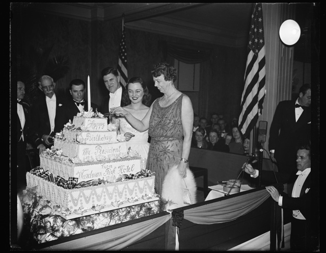 FIRST LADY CUTS PRESIDENT'S BIRTHDAY CAKE. WASHINGTON, D.C. JANUARY 30. AS A CLIMAX TO HER ATTENDANCE AT MANY OF THE PRESIDENT'S BIRTHDAY BALLS IN THE CAPITAL TONIGHT, MRS. ROOSEVELT CUTS THE OFFICIAL PRESIDENT'S BIRTHDAY CAKE AT THE WARDMAN PARK HOTEL. THIS WAS THE LAST CELEBRATION THE FIRST LADY ATTENDED BEFORE RETURNING TO THE WHITE HOUSE TO LISTEN TO THE PRESIDENT THANK THE NATION OVER THE AIR FOR THEIR INTEREST IN THE FIGHT AGAINST INFANTILE PARALYSIS. L TO R: MRS. E M. COLVIN, NIECE OF D.C. COMMISSIONER MELVIN HAZEN; MRS. EDGAR MORRIS, WIFE OF THE CHAIRMAN FOR THE D.C