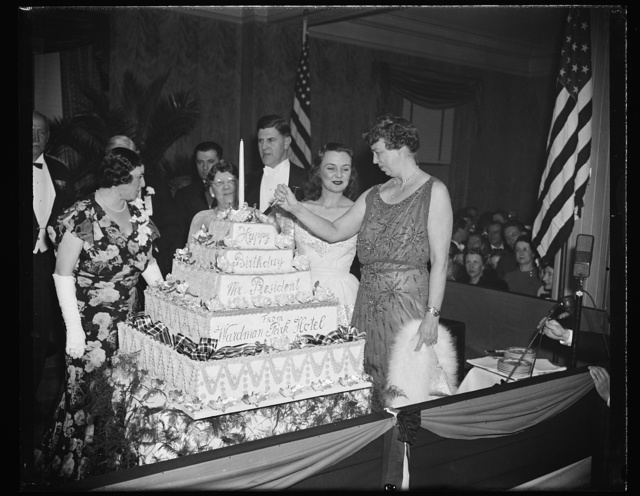 FIRST LADY CUTS PRESIDENT'S BIRTHDAY CAKE. WASHINGTON, D.C. JANUARY 30. AS A CLIMAX TO HER ATTENDANCE AT MANY OF THE PRESIDENT'S BIRTHDAY BALLS IN THE CAPITAL TONIGHT, MRS. ROOSEVELT CUTS THE OFFICIAL PRESIDENT'S BIRTHDAY CAKE AT THE WARDMAN PARK HOTEL. THIS WAS THE LAST CELEBRATION THE FIRST LADY ATTENDED BEFORE RETURNING TO THE WHITE HOUSE TO LISTEN TO THE PRESIDENT THANK THE NATION OVER THE AIR FOR THEIR INTEREST IN THE FIGHT AGAINST INFANTILE PARALYSIS. L TO R: MRS. E.M. COLVIN, NIECE OF D.C. COMMISSIONER MELVIN HAZEN; MRS. EDGAR MORRIS, WIFE OF THE CHAIRMAN FOR THE D.C. PRESIDENT'S BIRTHDAY BALLS, EDGAR MORRIS; ANDREA LEEDS, SCREEN STAR; AND MRS. ROOSEVELT