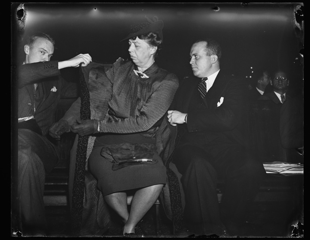FIRST LADY LISTENS TO TESTIMONY AT DIES COMMITTEE. WASHINGTON, D.C. NOVEMBER 30. PAYING A SURPRISE VISIT TO THE DIES HEARING TODAY WHERE SHE HEARD TESTIMONY CONCERNING THE AMERICAN YOUTH CONFERENCE, MRS. ROOSEVELT IS HELPED OUT OF HER COAT BY JACK McMICHAEL, CHAIRMAN OF THE ORGANIZATION, AND WILLIAM W. HINCKLEY, RIGHT, FORMER CHAIRMAN