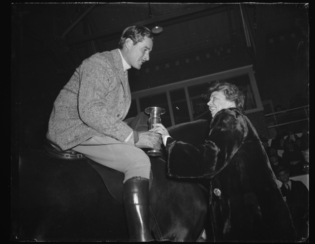 FIRST LADY PRESENTS TROPHY. WASHINGTON, D.C. JANUARY 25. ERROL FLYNN, STEPPING OUT OF HIS ROLE AS MOVIE STAR, TURNED HORSEMAN, AT THE FORT MYER PRESIDENT'S BIRTHDAY HORSE SHOW. MRS. ROOSEVELT PRESENTS THE HACK CLASS TROPHY WHICH HE WON