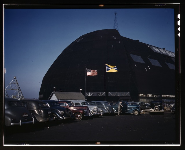 Formerly an aircraft dock, this huge building -- thought to be the largest in the world with no interior supports -- is now the scene of many busy shops turning out aircraft sub-assembly parts, Goodyear Aircraft Corp., Akron, Ohio. Either new housing close to the plant or vastly improved public transportation will eventually have to be supplied, for the tires on the cars of the workers, and perhaps even the cars themselves, will in many instances give in before the end of the present emergency