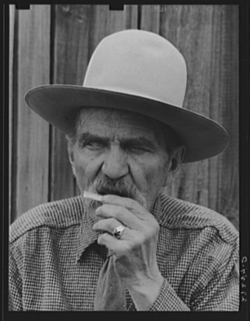 Frank Latta moistening a hand-rolled cigarette. Bozeman, Montana
