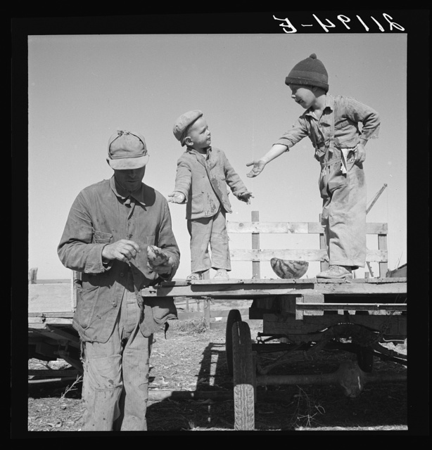 "Franklin Schroeder and the older boys in the yard. He is giving them the ""last watermelon of the season."" Dead Ox Flat, Malheur County, Oregon. General caption number 67-111"