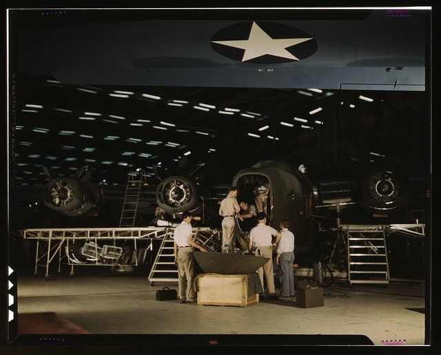Getting a nose door ready to put on a C-87 transport plane at the end of the assembly line at the Consolidated Aircraft Corporation plant, Fort Worth, Texas