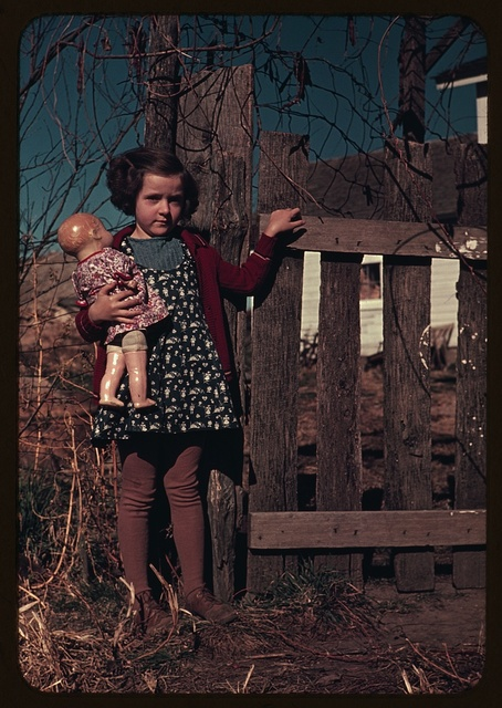 [Girl with doll standing by fence]