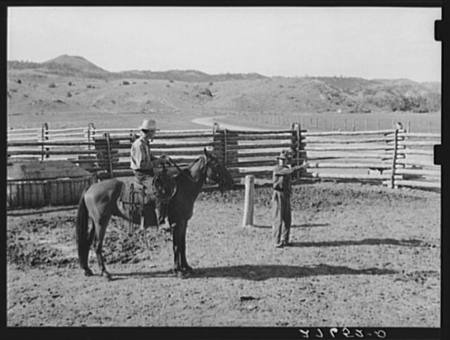 Giving directions to visiting cowhand. Quarter Circle 'U' Ranch, Montana