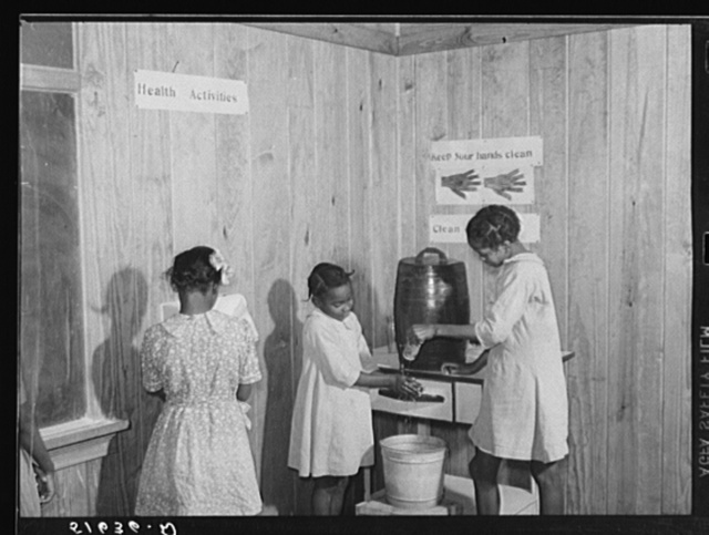 Gladys Crimer drying her hands on paper towel and Bernice Mathis and Edna Law washing theirs in clean-up corner in second and third grade school room. Flint River Farms, Georgia