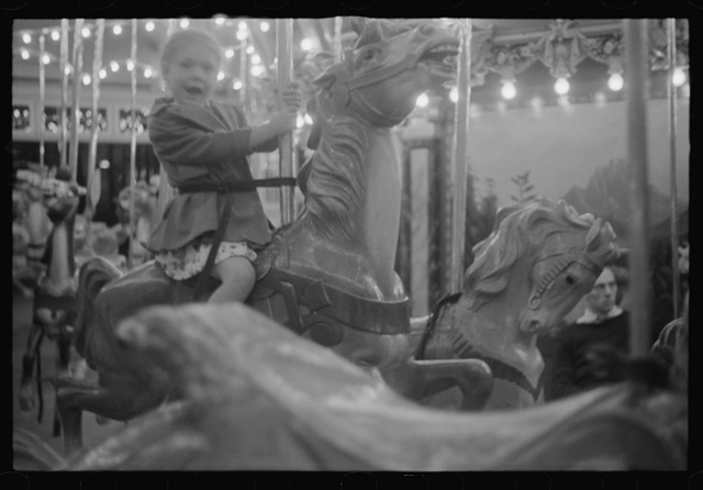 Glen Echo, Maryland. A small girl enjoying a ride on the merry-go-round at Glen Echo Park
