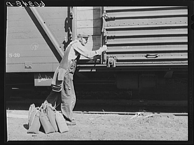 Grain sampler opening door of car of wheat after breaking seal. Minneapolis, Minnesota