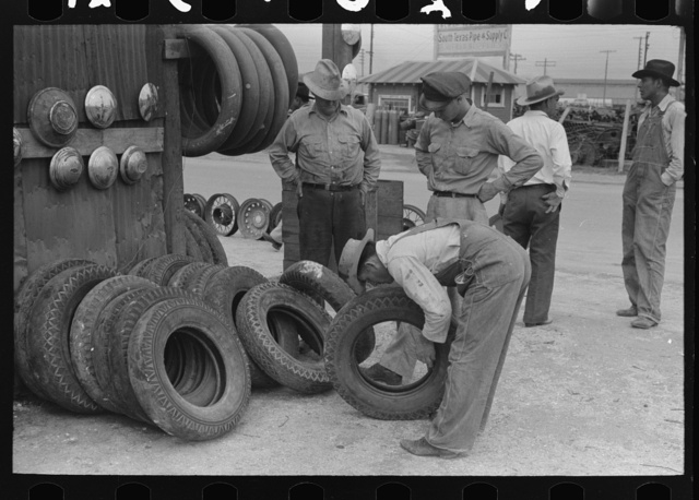 Group of men inspecting secondhand tires for sale, Corpus Christi, Texas
