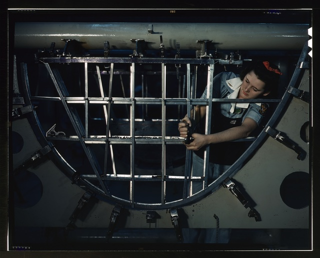 Helen Bray, who left school to become a mechanic at a western aircraft plant, is making an emplanage section on a new Consolidated transport, Consolidated Aircraft Corp., Fort Worth, Texas. This new ship, adapted from the B-24 bomber, is known as the C-87, carries one of the greatest human and cargo loads of any plane now in mass production
