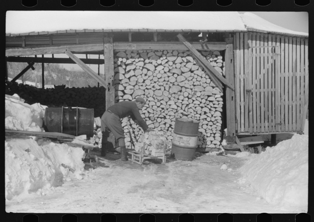 Hired hand on Mr. Dickinson's farm in Lisbon, near Franconia, New Hampshire, putting split logs in woodshed for winter fuel