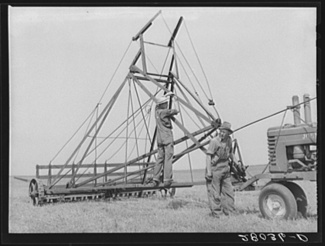 Hired hands fixing jayhawk hayloader. Kimberley farm, Jasper County, Iowa