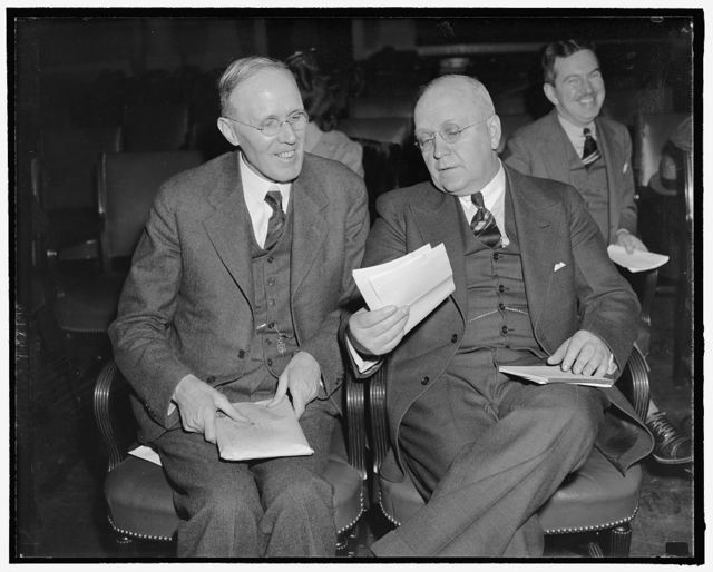 """Hit Townsend pension plan. Washington, D.C., Feb. 23. Dr. Harold G. Moulton, right, President of the Brookings Institution, today told the House Ways and Means Committee that the Townsend Old Age Pension Bill 'can readily be demonstrated to be fantastic' while Dr. Willford I. King, left, of New York University, declared that most pension plans, such as the Townsend Plan, do not """"add a dollar either to total demand or to total purchasing power,"""" 2-23-39"""