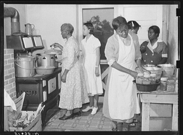 Home management and economics class canning peas with pressure cookers under supervision of Miss Evelyn M. Driver (in white uniform). Others are Ada Turner, Hattie Bowman, Louise Thomas and Mrs. Missouri Thomas, whose kitchen they are using. Flint River Farms, Georgia