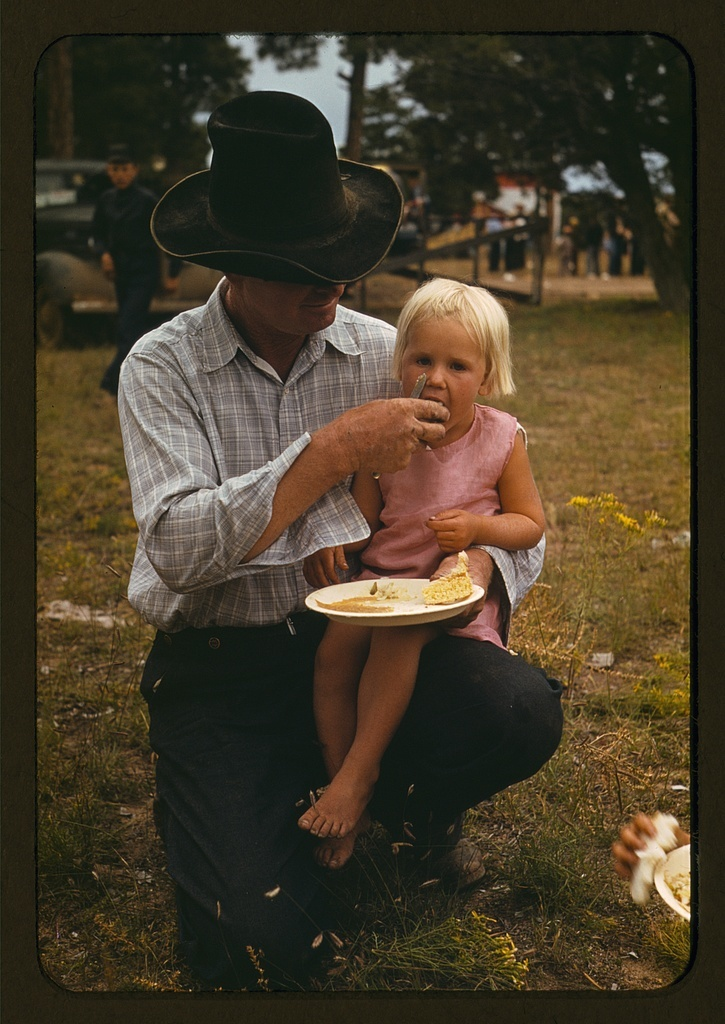 Homesteader feeding his daughter at the Pie Town, New Mexico Fair free barbeque