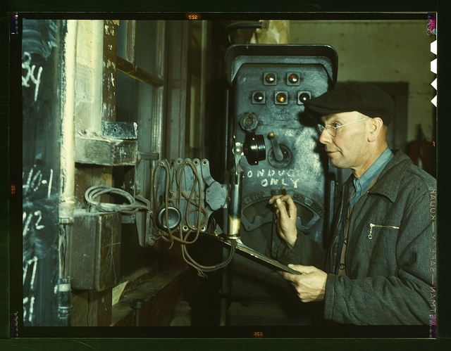 Hump master in a Chicago and Northwestern railroad yard operating a signal switch system which extends the length of the hump track. He is thus able to control movements of locomotives pushing the train over the hump from his post at the hump office; Chicago, Ill.