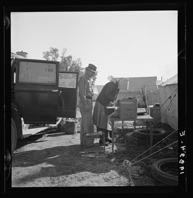 "In a carrot puller' camp near Holtville, Imperial Valley, California. Migratory laborers from Texas, packing up to leave camp because of work shortage. ""Don't take any pictures of us. We don't want any truck with Mr. Hearst."""