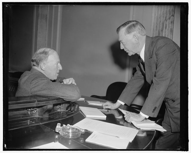 In huddle. Washington, D.C., Feb. 21. Assistant Secretary of State Francis B. Sayre, left, in a huddle with Senator Key Pittman following Sayre's Appearance before the Senate Territorial and Insular Affairs Committee today in support of amendments to the Tydings-McDuffie Independence Act. Sayre told the Committee vital interests of the U.S. in the Far East were concerned in the disposition of the Philippines, 2-21-39