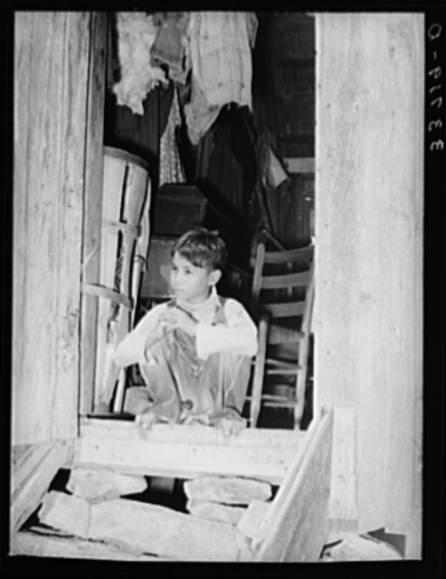 "Indian child ""hunkering down"" in doorway of farm home near Sallisaw, Oklahoma. Hunkering down is an Indian slang term for this way of sitting on your heels"