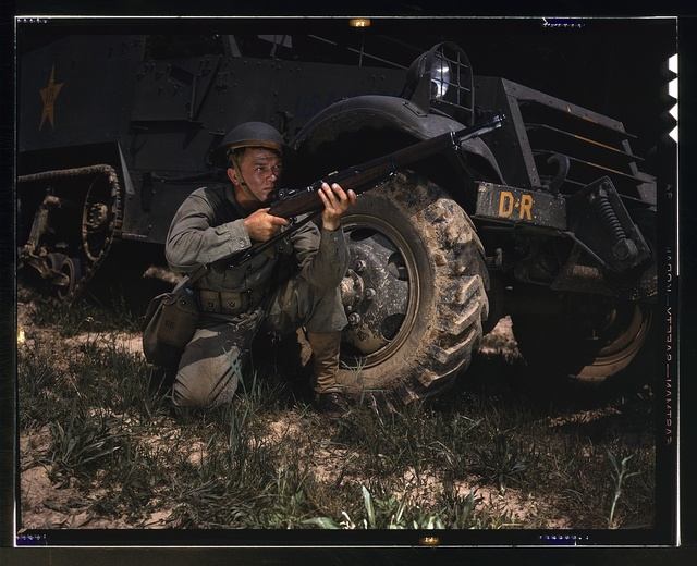 Infantryman with halftrack, a young soldier of the armed forces, holds and sights his Garand rifle like an old timer, Fort Knox, Ky. He likes the piece for its fine firing qualities and its rugged, dependable mechanism.