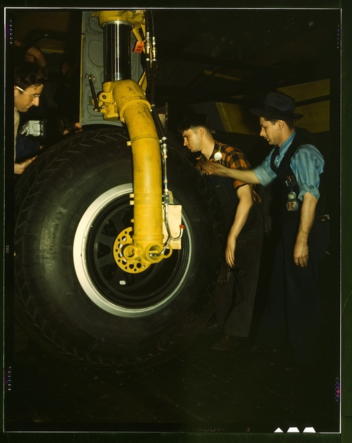Inspecting of landing wheel of the transport planes at Willow Run
