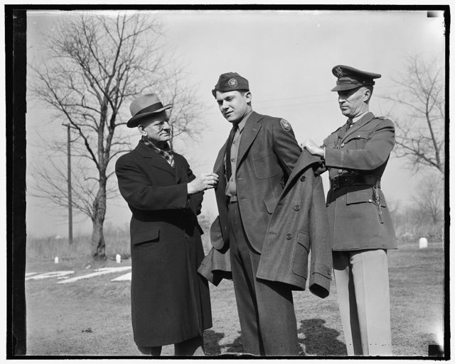 Inspects new CCC uniform. Washington, D.C., Feb. 1. Robert E. Fechner, left, Director of the Civilian Conservation Corps, inspecting the new uniform issued to members of the Corps for the first time today. The outfit consists of a two-button pleated back, sack coat of spruce green topped off with new style overseas cap and a red an yellow CCC insignia on left shoulder. Frank Papuga is wearing uniform while on right is Lt. Col. Thomson Lawrence, in command of Central District, 3rd. corps area