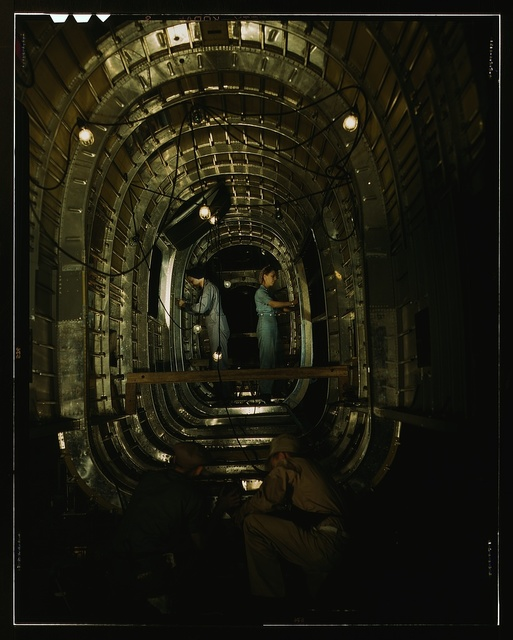 Installing structural parts of a C-87 transport plane in the tunnel of a tail fuselage section at the Consolidated Aircraft Corporation plant, Fort Worth, Texas