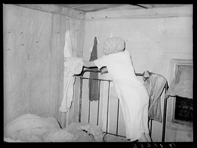 Interior of migrant's home near Muskogee, with mother removing articles of clothing preparatory for departure to California. Oklahoma